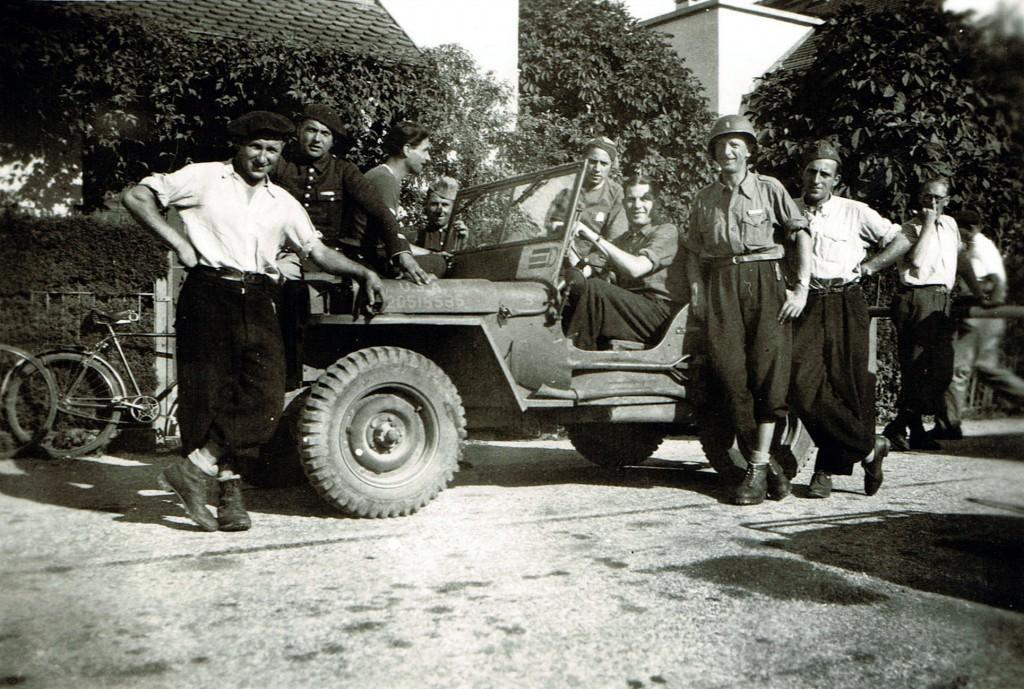 Ferney, 1944 (date à préciser): Première Jeep US venue du nord pour récupérer des internés à la frontière suisse. Pour la photo, le chauffeur américain (casque) a cédé le volant à Raymond Chaffard. A gauche, on reconnaît M. Lachaux (Ornex) et François Baillet, officier du 24è BCA et bientôt directeur de l'école. A droite du soltadt américain, Jaja Pusterla. (Collection Pierre Grenier).