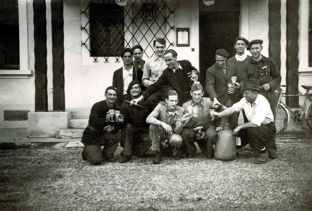 1944: Devant l'hôtel du Capucin gourmand tenu par Jean Viens (à droite, servant à boire), les deux aviateurs américains à peine libérés d'un long internement en Suisse et un groupe de Ferneysiens parmi lesquels Albert Ailloud, Edmond Vivert, Lulu Bourgeois, René Pusterla, et M. Lachaux d'Ornex (prénom à préciser. PGR 108, collection Pierre Grenier.