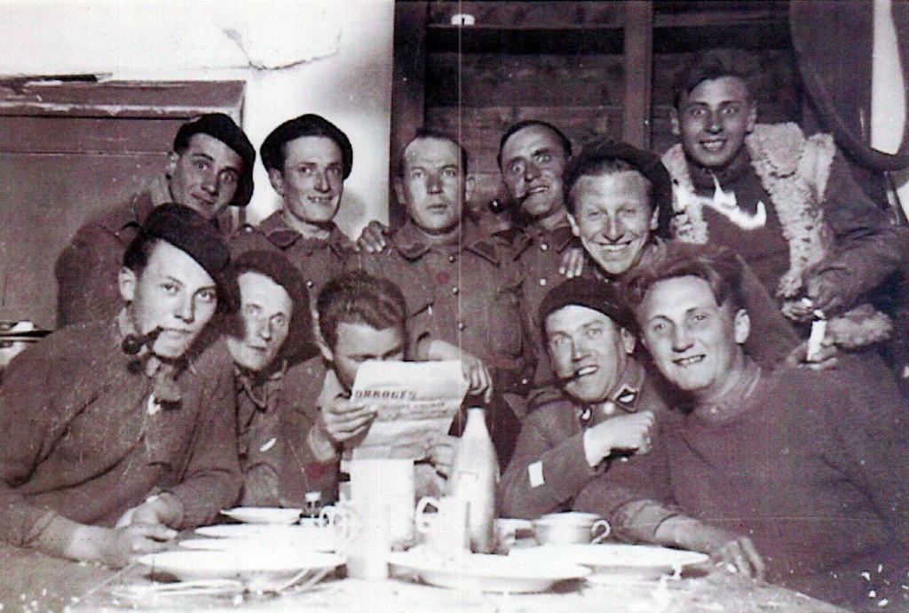 """8 Mai 1945: Ferneysiens du 24è BCA dans les Alpes (Meyronnes). De g.à dr.: René Chappelu, M. Cattoir (peintre à Gex), Albert Baud (Hôtel Bellevue, Francis Carme, Pierre Grenier (lisant les Allobroges), François Baillet, Jouvenod (Parisien réfugié à Segny), Diamant dit pépé-la-pioche, """"Bouteille""""."""