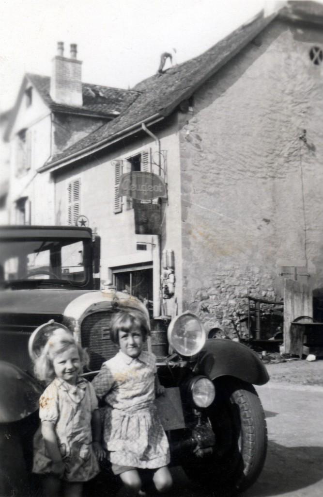 """Le garage Dunand en 1948, au 11 rue de Versoix. A l'angle de la maison, on distingue le fût d'essence, vendue à la pompe à main, 5 litres à la fois. Agence Peugeot (panneau) mais la voiture est une des deux Citroen C6 d'Antonin Dunand. Celle-ci date de 1928 et, après suppression de la carroserie arrière, deviendra une dépanneuse équipée d'une """"chèvre"""" de levage. Au premier plan, Roland (1944) et Gabriel """"Gaby"""" (1942) Dunand. (GBY005, archives Gabriel Dunand)"""